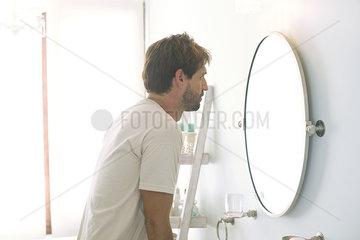 Man looking at self in bathroom mirror