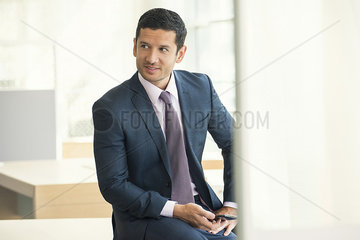 Businessman sitting with smartphone in hand  looking away and smiling