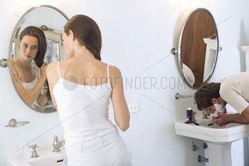Woman brushing hair  husband shaving