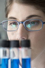 Scientist looking at test tubes in lab  close-up