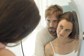 Couple cheek to cheek  looking at each other in mirror