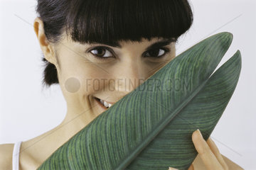 Young woman holding leaf in front of face  smiling  portrait