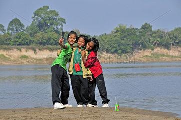 Drei Maedchen fotografieren sich mit dem Handy