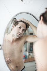 Man examining hairline in mirror