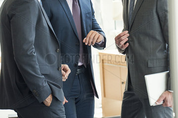 Businessmen standing chatting before meeting