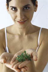 Young woman holding handful of fresh thyme  smiling at camera