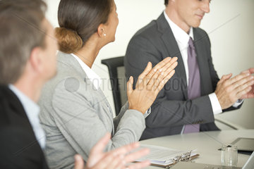 Executives clapping in meeting