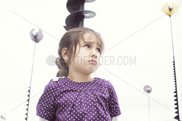 Little girl outdoors with sulky expression