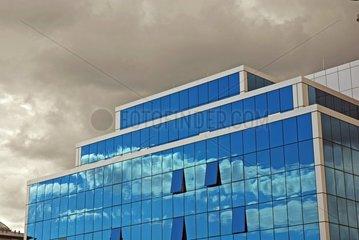 Himmelsspiegelungen auf einer Glasfassade eines Buerohauses im baden-wuerttembergischen Ulm