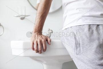 Man leaning against bathroom sink