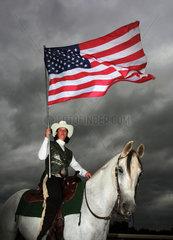 Hannover  Deutschland  Westernreiterin haelt die Nationalfahne der USA hoch