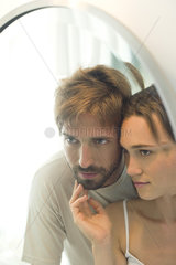 Couple looking into mirror together  wife caressing husand's bearded chin