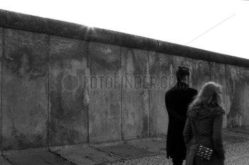 Berlin  Deutschland  Mann und Frau laufen an einem Teil der ehemaligen Grenzmauer vorbei
