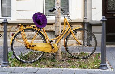 Gelbes Hollandfahrrad mit lila Damenhut