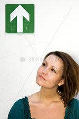 Berlin  Deutschland  zuversichtlich blickende junge Frau vor Pfeil-Piktogramm