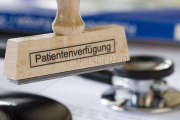 Stempel mit Aufschrift Patientenverfuegung haengt an Stempelrondell vor einem Stethoskop