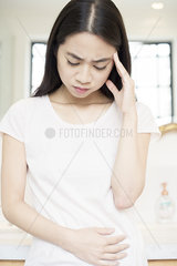 Woman with hand on stomach  looking down in pain