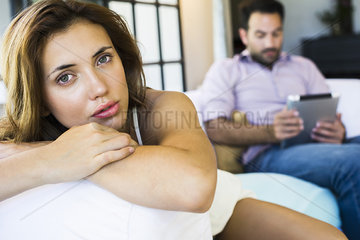 Woman displeased by boyfriend on digital tablet