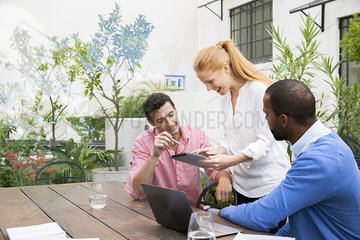 Businesswoman using digital tablet to present ideas to team members