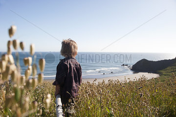 Child looking at tranquil beach view