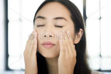 Woman touching her face  eyes closed
