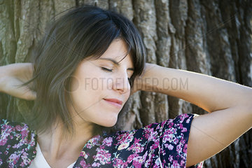Woman resting head on tree trunk  eyes closed