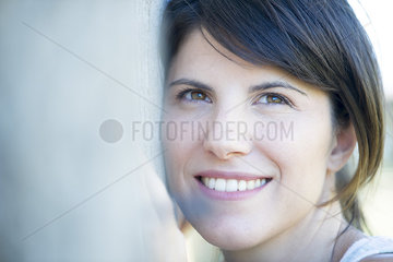 Woman resting head on tree trunk  smiling cheerfully