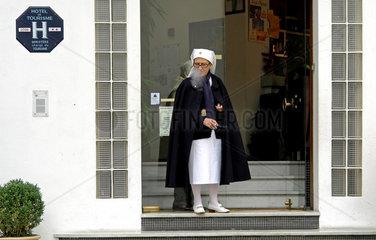Rauchende Ordensschwester vor Hotel in Lourdes