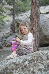 Girl sitting on rock  smiling cheerfully