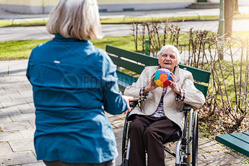 Woman taking care of old woman in wheelchair playing with ball in park