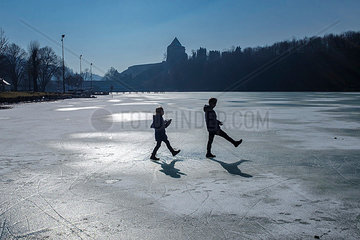 Two children playing on icy surface