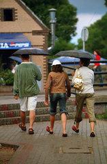 Familie beim Urlaub spaziert bei Regenwetter durch Leba  Polen