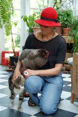 Frau mit rotem Hut  Huhn und Hauskatze