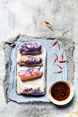Vegan rice paper wraps (vietnamese summer rolls)  filled with cabbage  carrots  bell pepper  rice noodles  and dipping sauce