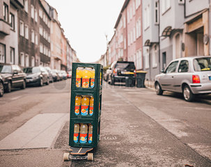 Stack of three boxes with lemonade bottles standing on longboard on the street