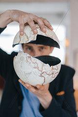 Man holding broken globe