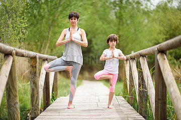 Mother and daughter doing yoga on boardwalk