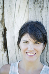 Woman leaning against tree trunk  smiling cheerfully  portrait