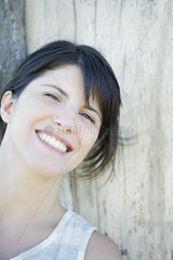 Woman leaning against tree trunk  smilling cheerfully  portrait