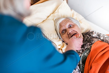 Woman taking care of old woman lying in bed