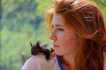 Portrait of redheaded teenage girl with squirrel on her shoulder