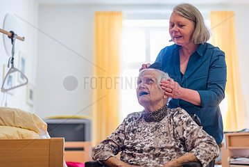 Woman taking care of old woman brushing her hair