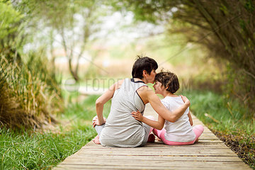 Rear view of mother kissing daughter on boardwalk