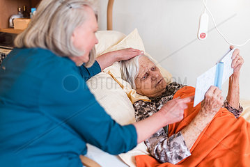 Woman taking care of old woman lying in bed reading book