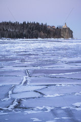 Frozen ice patterns on Lake Superior during magenta sunset with iconic Split Rock lighthouse in distance  Two Harbors  MN  USA