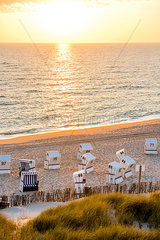 Germany  Schleswig-Holstein  Sylt  beach and empty hooded beach chairs at sunset