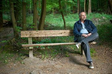Mann auf einer Parkbank im Wald