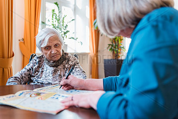 Woman taking care of old woman doing crossword puzzle