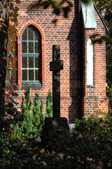 Berlin  Deutschland  Silhouette eines Grabkreuzes vor der Friedhofskapelle auf dem Friedhof Grunewald