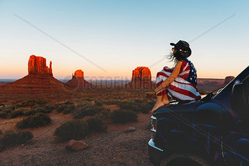 USA  Utah  Woman with United States of America flag enjoying the sunset in Monument Valley